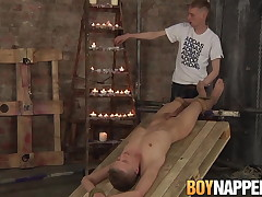 Bound up twink gives footjob to master..